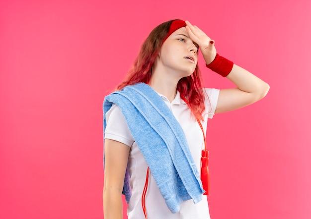 어깨에 수건으로 머리띠에 젊은 스포티 한 여자는 분홍색 벽에 피곤하고 지쳐 서 찾고