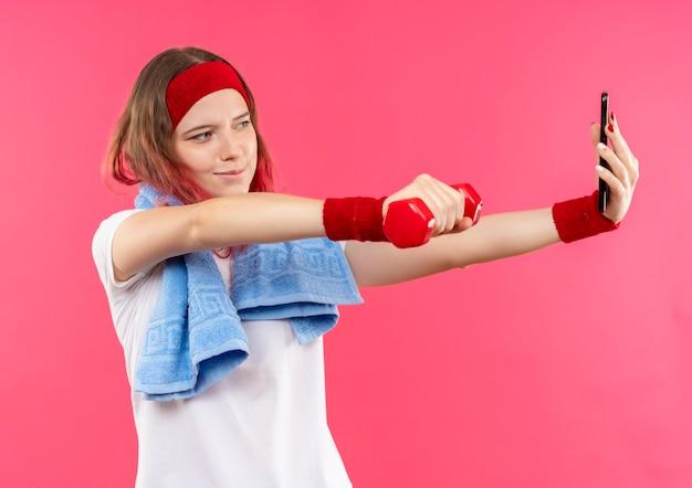ピンクの壁の上に立っている彼女のスマートフォンのカメラに手にダンベルを見せて自分のselfieを取っている肩にタオルを持ったヘッドバンドの若いスポーティな女性