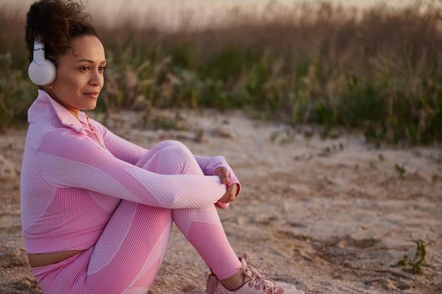 Молодая спортивная женщина в розовой спортивной одежде наслаждается красивой природой, сидя на берегу реки