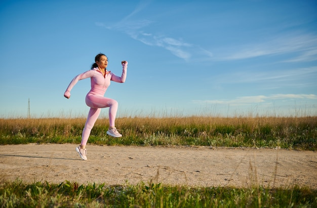 Молодая спортивная женщина в розовой спортивной одежде, бегающей трусцой на открытом воздухе в красивый солнечный ранний летний день. спорт. концепция здоровья, выносливости и кардиотренировки с копией пространства