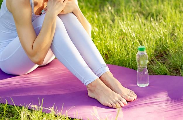 Молодая спортивная женщина в белой спортивной питьевой воде после тренировки