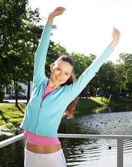 若いスポーティな女性は屋外にジャンプします