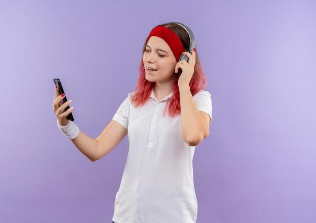 Giovane donna sportiva che ascolta musica con le sue cuffie guardando lo schermo del suo smartphone sorridente in piedi sopra la parete viola