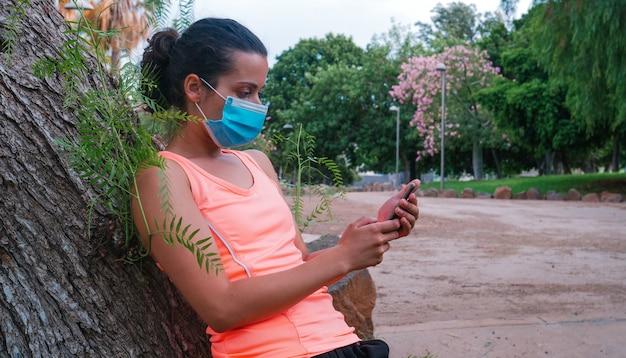 公園で運動を終えた後、携帯電話を見ている若いスポーティな女性