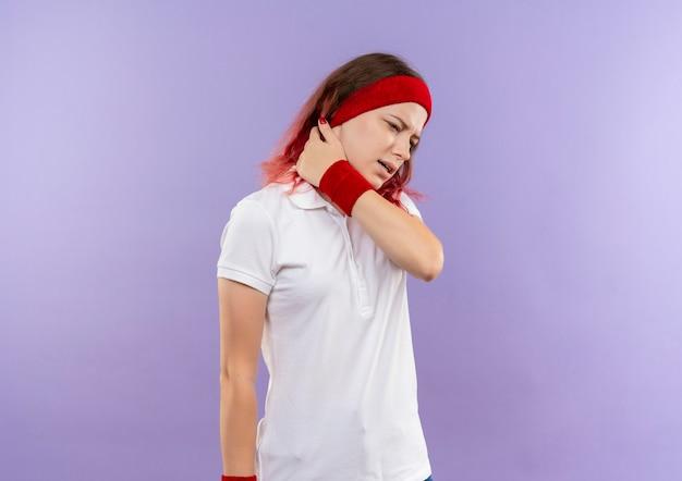 Giovane donna sportiva in cerca di malessere toccando il suo collo sensazione di dolore in piedi sopra la parete viola