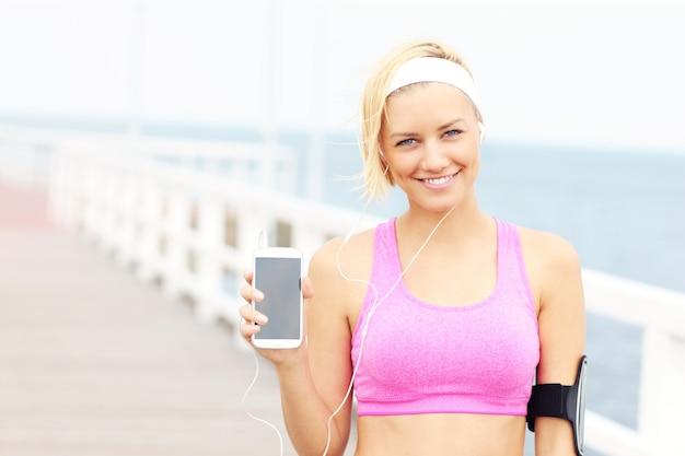 Молодая спортивная женщина на пирсе над морем, держа телефон