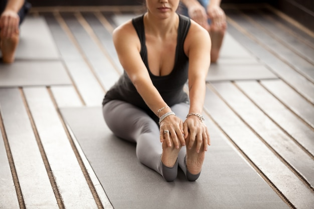 Young sporty woman in paschimottanasana pose