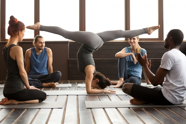 Young sporty woman in pincha mayurasana pose and a group