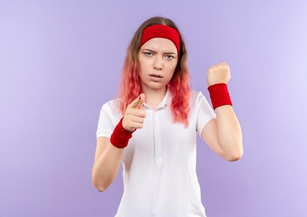 紫色の壁の上に立っている深刻な顔で拳を握りしめカメラに人差し指で指している若いスポーティな女性