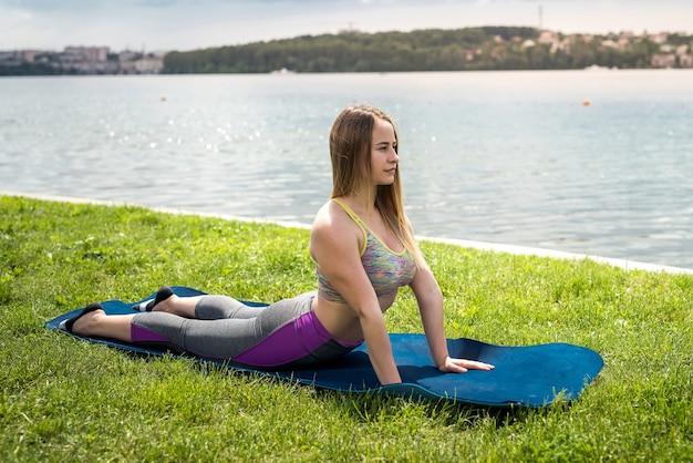朝、湖のほとりのヨガマットでアーサナ体操と筋肉のストレッチを練習している若いスポーティな女性。健康的な生活様式