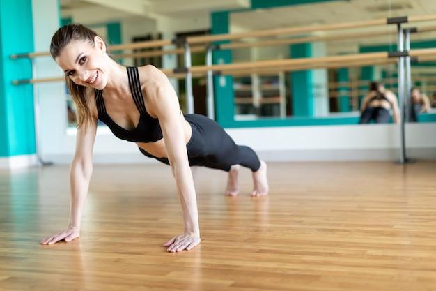 젊은 스포티 한 여자 연습, 십자 운동, 자전거 위기 포즈, 운동, 운동복, 검은 색 바지와 탑, 실내 전체 길이를 입고.