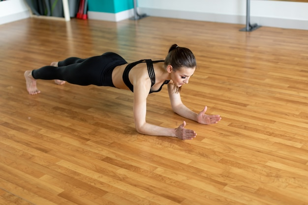 Young sporty woman practicing, doing crisscross exercise, bicycle crunches pose, working out, wearing sportswear, black pants and top, indoor full length.