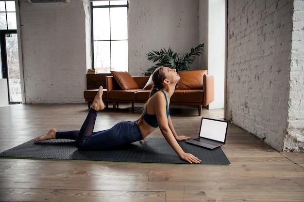 요가를 연습하고 온라인 수업 또는 가상 자습서를 위해 노트북을 사용하여 집에서 몸을 스트레칭하는 젊은 스포티 한 여자. 고품질 사진