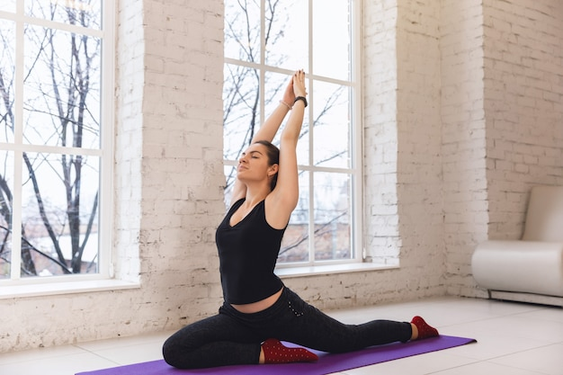 Young sporty woman practicing yoga near the window, doing one legged pigeon exercise