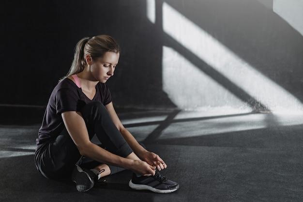 若いスポーティな女性は、トレーニングの準備をします。靴ひもを結ぶ女の子。