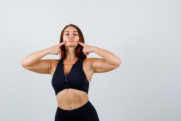 Молодая спортивная женщина, прижав ее щеки