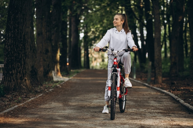 Young sporty woman riding bicycle in the park