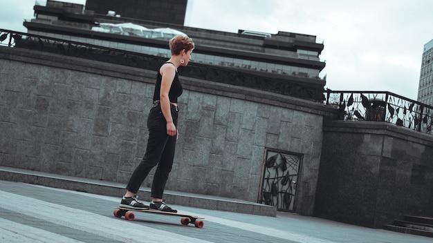 Молодая спортивная женщина катается на лонгборде в парке