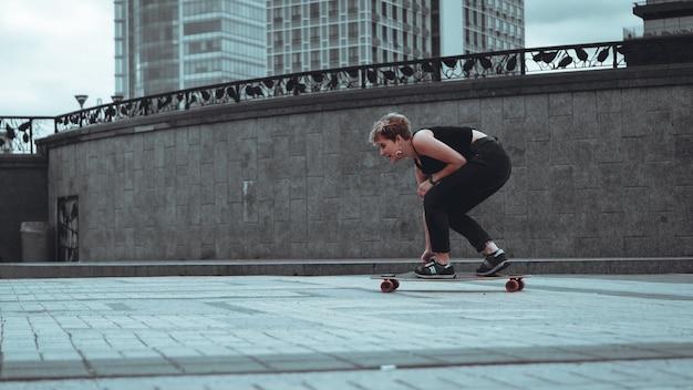 公園のロングボードに乗って若いスポーティな女性