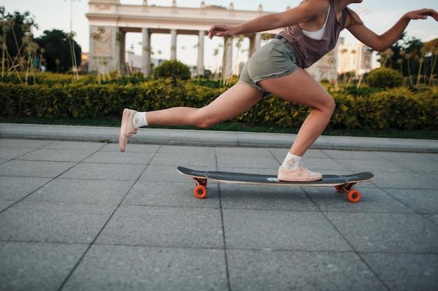 Молодая спортивная женщина, едущая на longboard в парке.