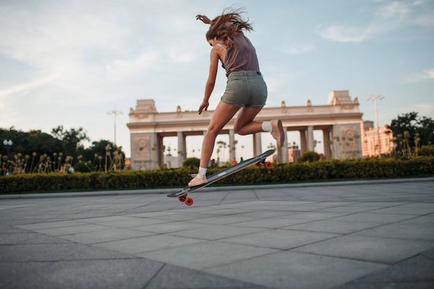 Молодая спортивная женщина катается на скейтборде longboard в парке