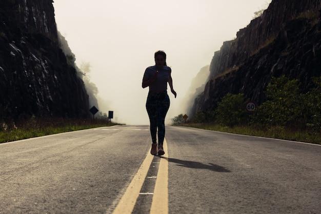 霧の早い朝に走る若いスポーティな女性