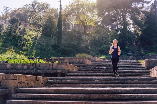 Молодая спортивная женщина, бегущая вниз по лестнице утром в парке, утренняя тренировка на открытом воздухе, спорт и здоровый образ жизни