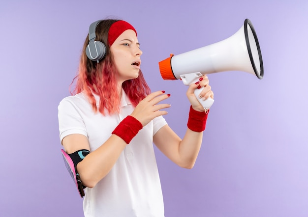 Young sporty woman shouting to megaphone loking aside standing over purple wall