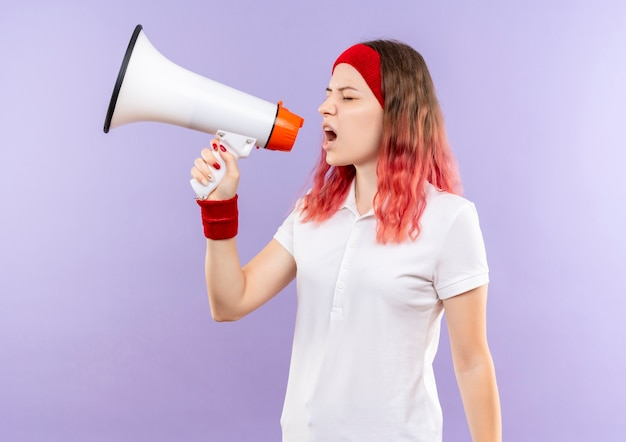 Giovane donna sportiva che grida al megafono con espressione aggressiva in piedi sopra la parete viola