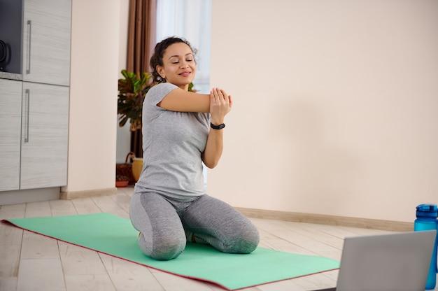 젊은 스포티 한 여자는 피트니스 매트에 앉아 폐쇄 동안 집에서 운동하는 동안 왼쪽으로 그녀의 몸을 스트레칭