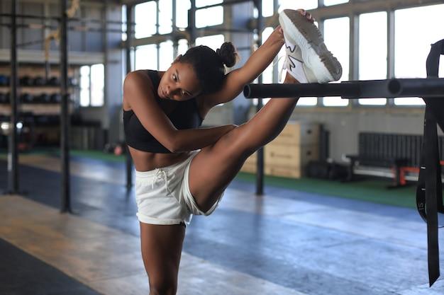 체육관에서 스트레칭 하는 젊은 스포티 한 여자.