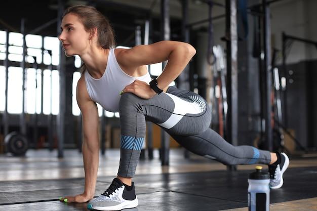 Молодая спортивная женщина, растягивающаяся в тренажерном зале