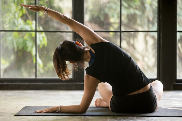 Young sporty woman in sukhasana side bending pose