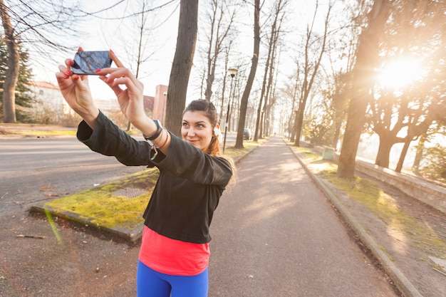 Young sporty woman taking a selfie at park