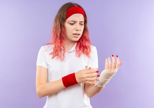 보라색 벽 위에 서있는 그녀의 붕대 손목 느낌 통증을 만지고 젊은 스포티 한 여자