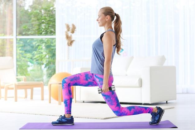 Молодая спортивная женщина тренируется дома