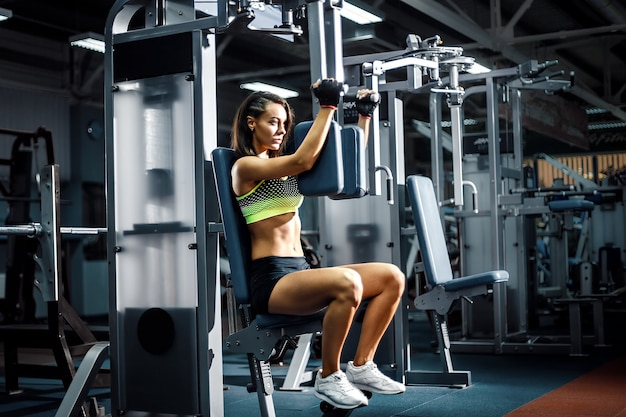 Young and sporty woman using pectoral fly machine