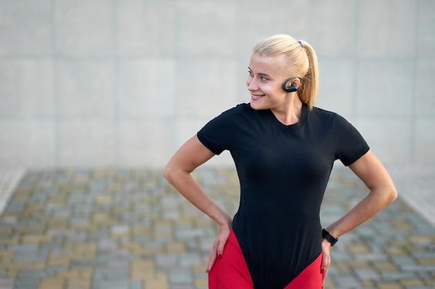 Молодая спортивная женщина в черной спортивной одежде и стильных красных леггинсах слушает музыку