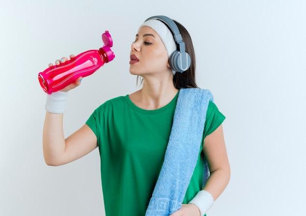 어깨에 수건으로 머리띠와 팔찌와 헤드폰을 착용하는 젊은 스포티 한 여자