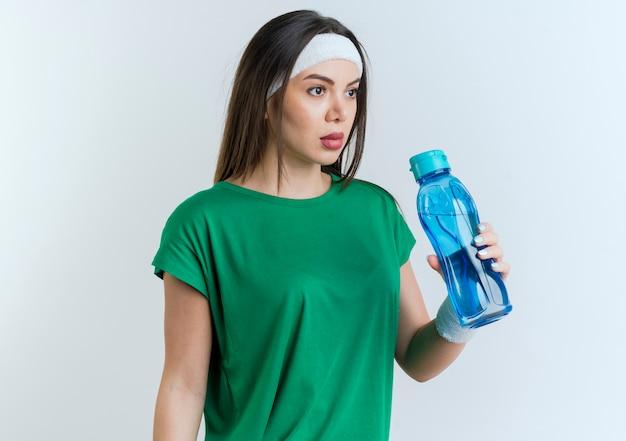 머리띠와 똑바로 보이는 물병을 들고 팔찌를 착용하는 젊은 스포티 한 여자