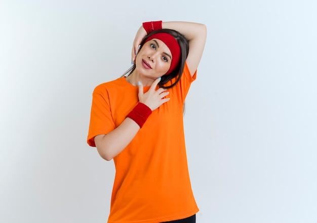 머리띠와 손목 밴드를 착용하는 젊은 스포티 한 여자는 고립 된 운동을하는 머리 주위에 팔을 넣어 찾고 측면으로 기울고
