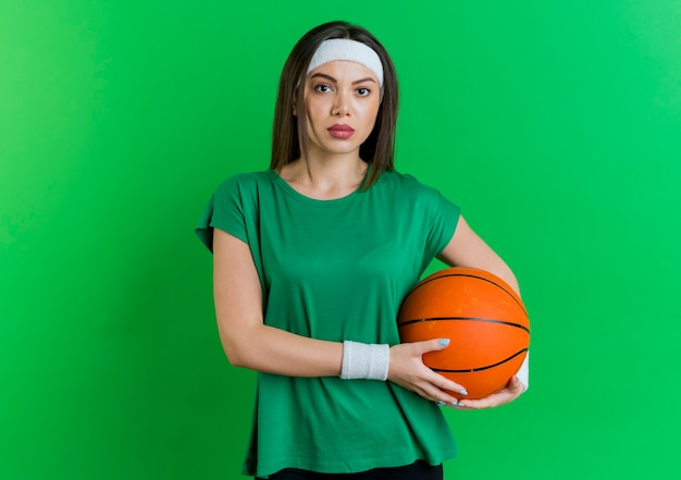 Giovane donna sportiva che indossa la fascia e braccialetti tenendo palla da basket e guardando