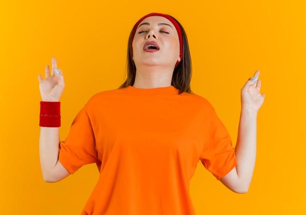Giovane donna sportiva che indossa la fascia e braccialetti mantenendo le mani in aria con gli occhi chiusi