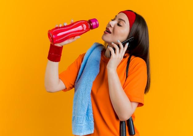 Giovane donna sportiva che indossa fascia e braccialetti con corda per saltare e asciugamano sulle spalle tenendo la bottiglia e parlando al telefono cercando di bere acqua