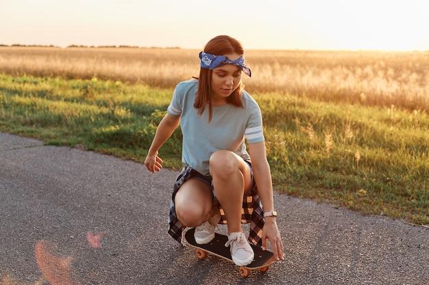 스케이트보드에 쪼그리고 앉는 티셔츠와 헤어밴드를 입은 젊은 스포티 여성, 여름에는 아스팔트 도로에서 롱보드를 타고, 일몰 시간을 적극적으로 보냅니다.