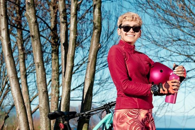 ボトルから水を飲みながら森で休んでいるヘルメットを持つ若いスポーティな女性