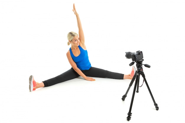 The young sporty woman with a fair hair in a black sports topic, black leggings and bright sneakers does an extension of muscles in front of the camera.