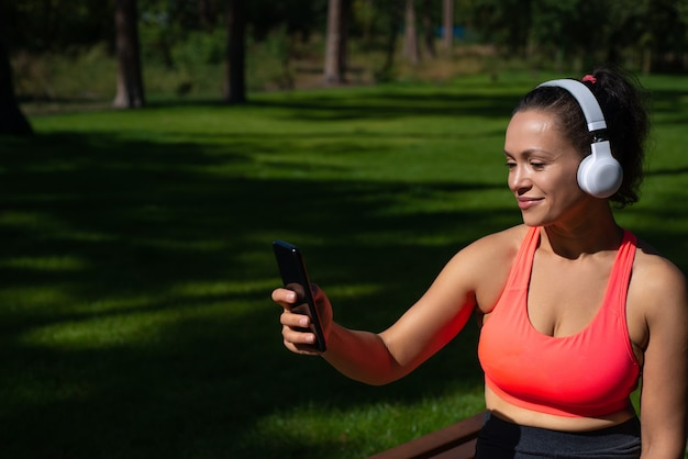 Young sporty woman with headphones holding smartphone and cheking playlist while listening to the music in the city park