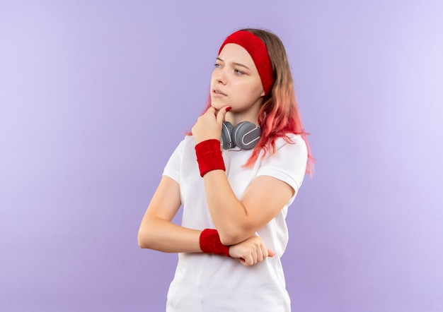 Молодая спортивная женщина с наушниками смотрит в сторону с рукой на подбородке, думая, стоя над фиолетовой стеной