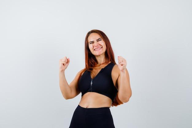Giovane donna sportiva con i capelli lunghi in un top nero